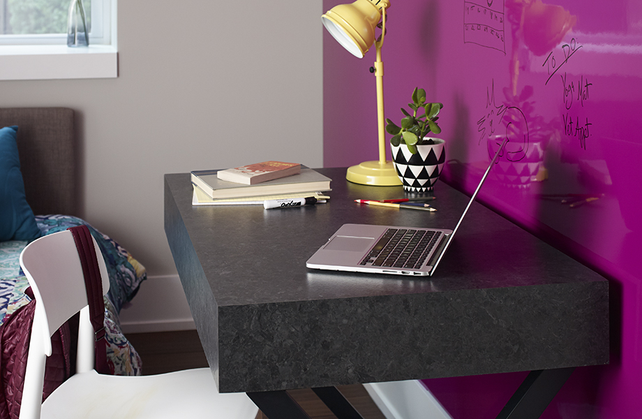 Laptop on desk with 527-34 Black Shalestone top against Formica® Writable Surfaces wall in 6907-90 Amarena
