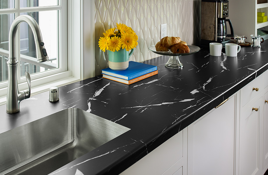 Modern kitchen with black and white 7403-11 Nero Marquina 180fx® laminate countertops, sink and coffee accessories paired with white cabinets
