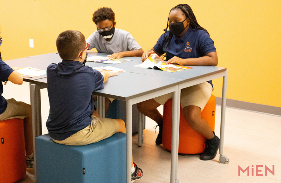 Four students on stools at Formica Laminate classroom table designed by MiEN