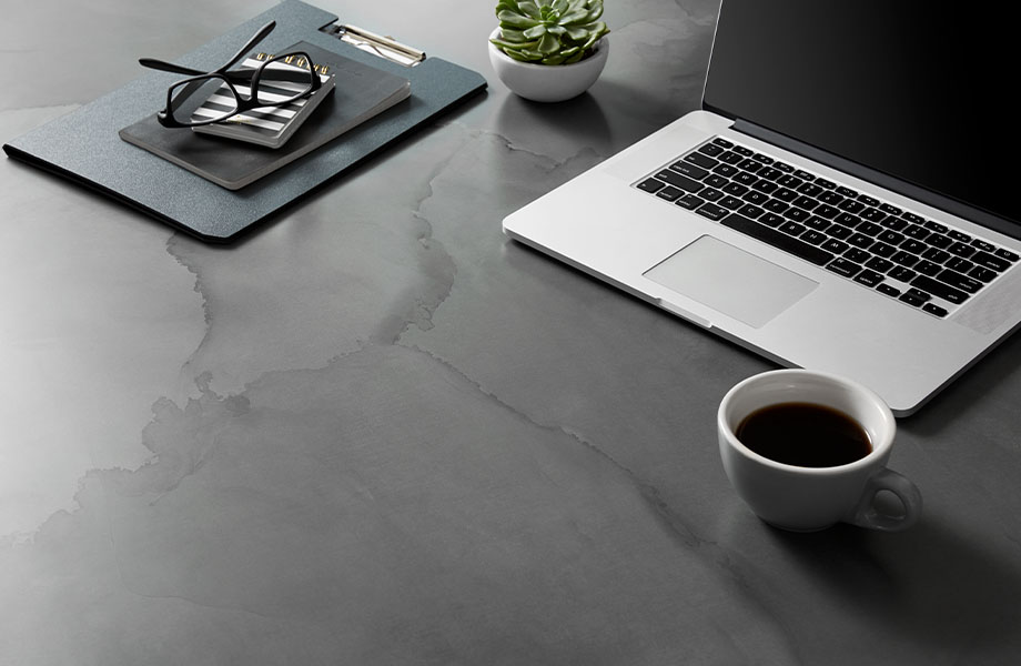 Table surface made with Formica® HPL laminate 180fx® 5017-11 Watercolor Steel – a blend of warm and cool grays with hints of blue and charcoal black as seen in tempered steel, a perfect pattern for the moody and inky tones in interiors today. Cup of coffee, notebook, plant, glasses, laptop