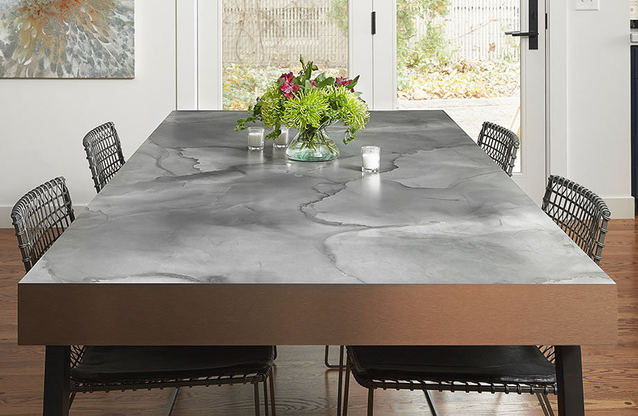 Dining room table surface made with Formica® HPL laminate 180fx® 5017-11 Watercolor Steel – a blend of warm and cool grays with hints of blue and charcoal black as seen in tempered steel, a perfect pattern for the moody and inky tones in interiors today.