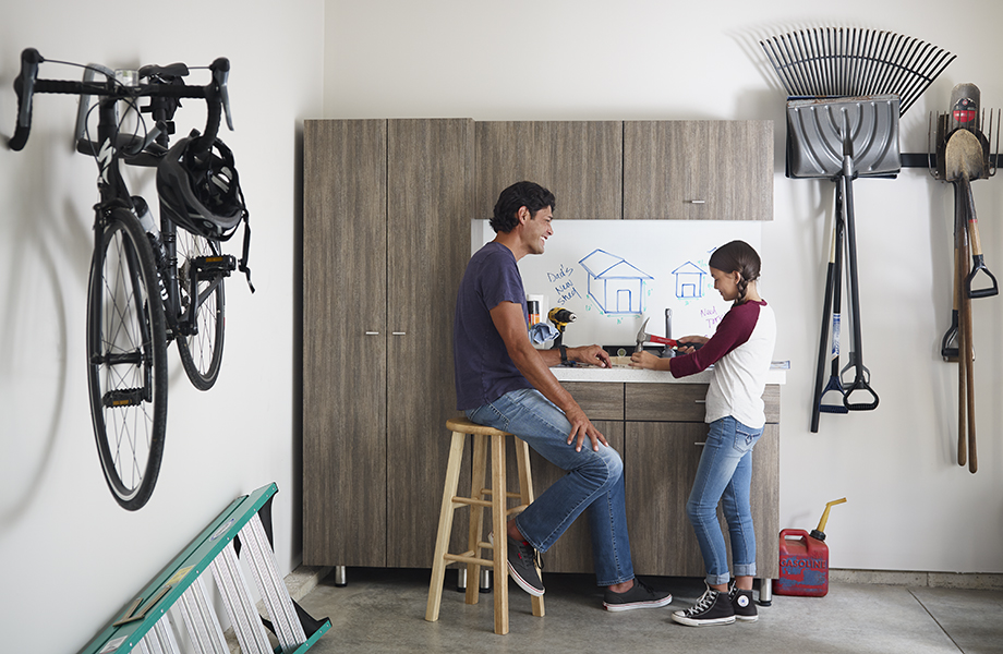 Father and daughter in garage with 8915-NG Walnut Fiberwood cabinets and 9313-90 ImagiGrid markerboard
