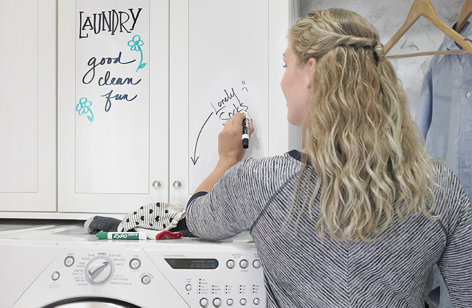 Woman in laundry room with 949 White Markerboard cabinets