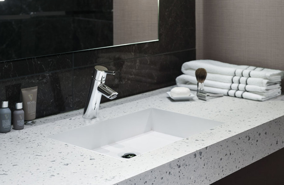 Hotel bathroom vanity with 8812-PA Tinted Paper Terrazzo eco-friendly countertops and nearby mirror, towels and toiletries