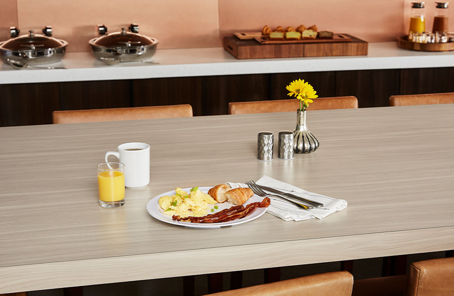 Buffet breakfast on communal table with 5793-NG Buff Elm light woodgrain laminate showcases post-pandemic hospitality design