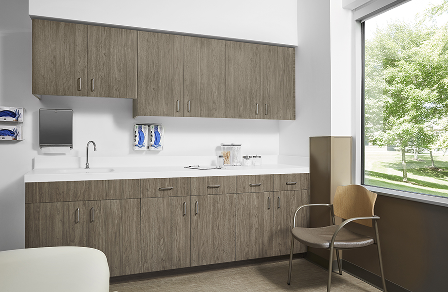 Patient room with chair, 5788-NG Hazel Walnut cabinetry and 408 Luna Brite White acrylic solid surface countertops