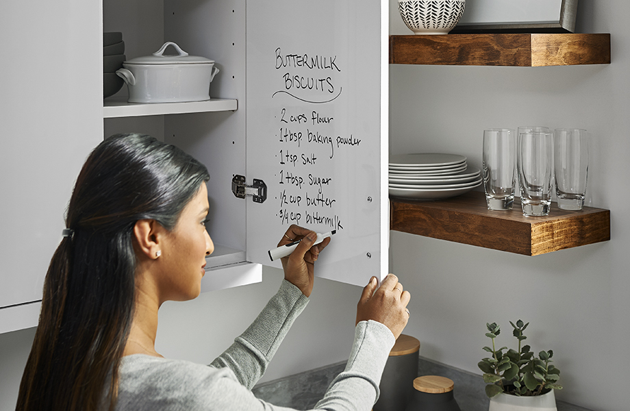 Woman writing on inside of White Markerboard kitchen cabinet