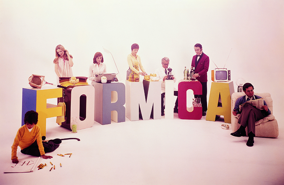 Large Formica laminate letters in multiple colors with people surrounding them