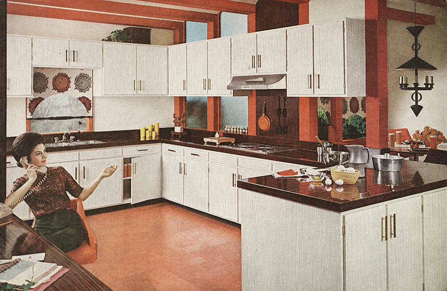 Woman in vintage kitchen with white Formica laminate cabinets, woodgrain countertops and orange floor