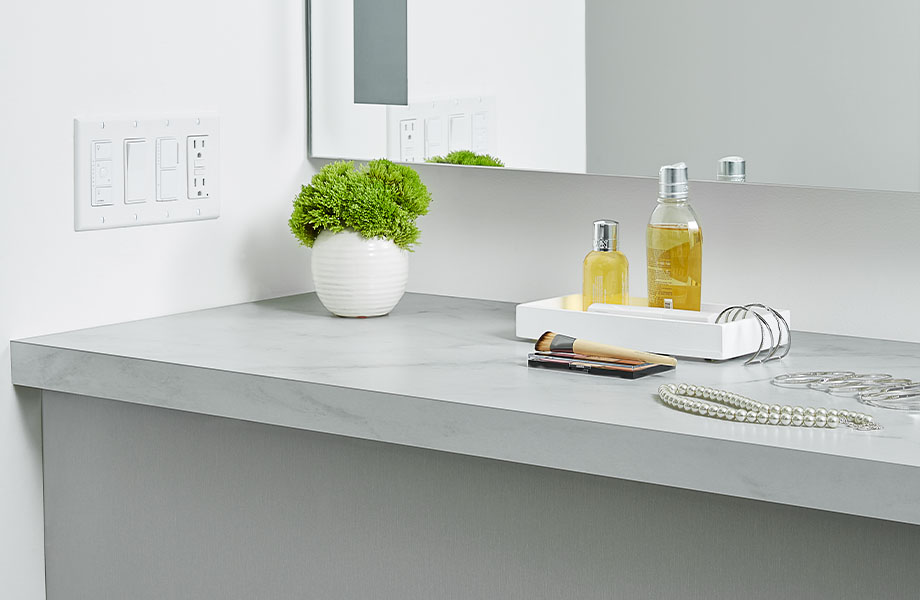 5018-11 Calacatta Cava, 9318 BH Aluminum bathroom vanity countertop displayed with a plant, mirror and jewelry