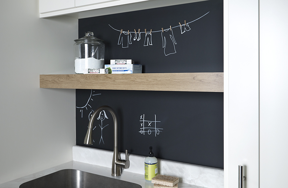 Black chalkboard laminate with open shelving above sink