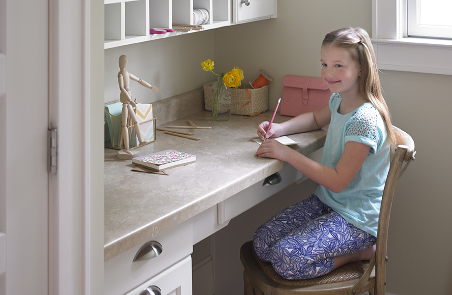 Girl sitting at desk with Formica® Laminate in 3526 Travertine