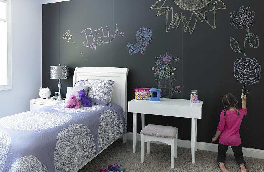 Niña dibuja en la pared de la recámara de las Superficies para Escribir Formica F3037 Black ChalkAble  cerca de la cama y del escritorio.