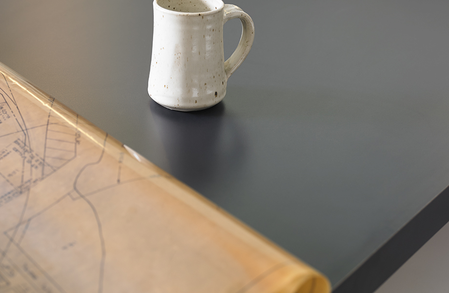 Aquí se muestra Nocturne 5323-AN  en la cubierta de la mesa con taza y planos.