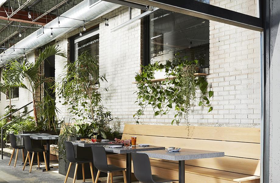Mesas de Superficie Sólida Everform 411 Grafite Terrazzo Matrix en exterior con sillas y plantas
