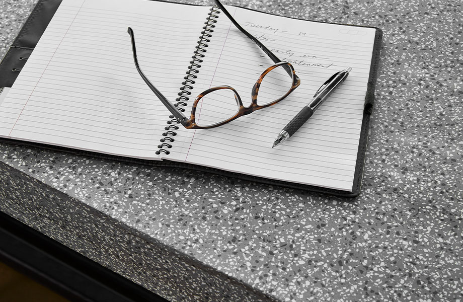 411 Grafite Terrazzo Matrix solid surface countertops with notebook and glasses