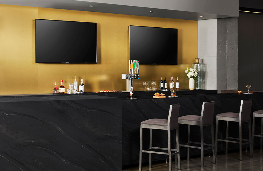 5015-11 Black Painted Marble bar top with M6423 Brushed Brass laminate accent wall panels, TVs and chairs