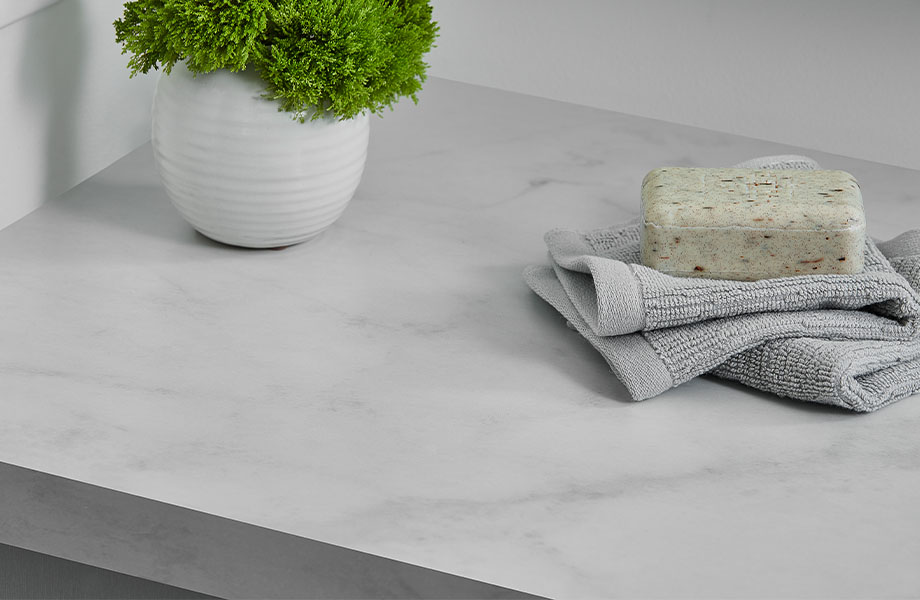 White countertops with 5018-11 Calacatta Cava showing soap, towel and plant