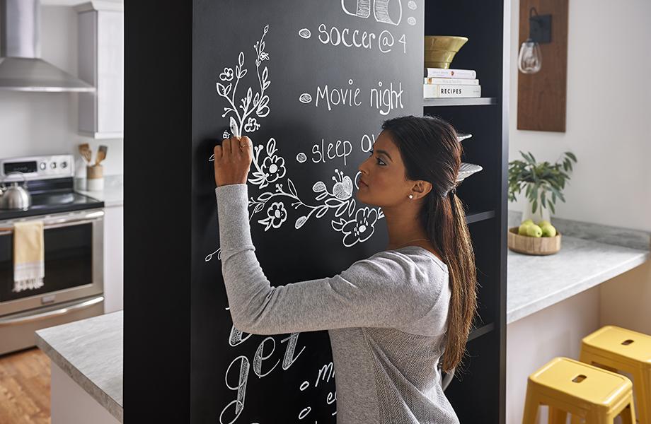 Femme utilisant un mur de craie dans une cuisine