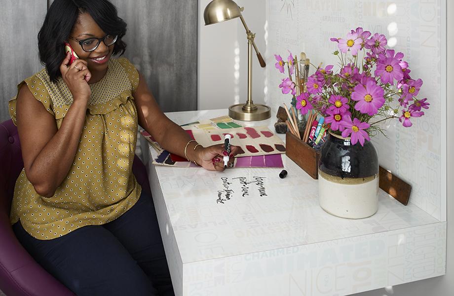 Femme assise à un bureau avec surfaces inscriptibles Formica® 9541-90 Happy Words et portes de placard en stratifié 9524-NG Chêne Ombré