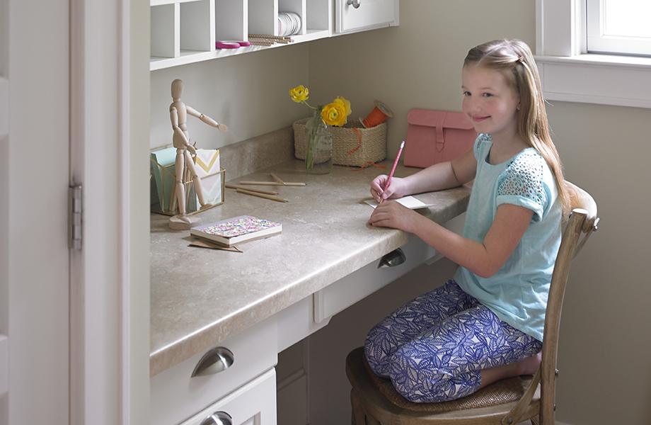 Fille assise à un bureau fabriqué avec du stratifié Formica® Travertin (3526)