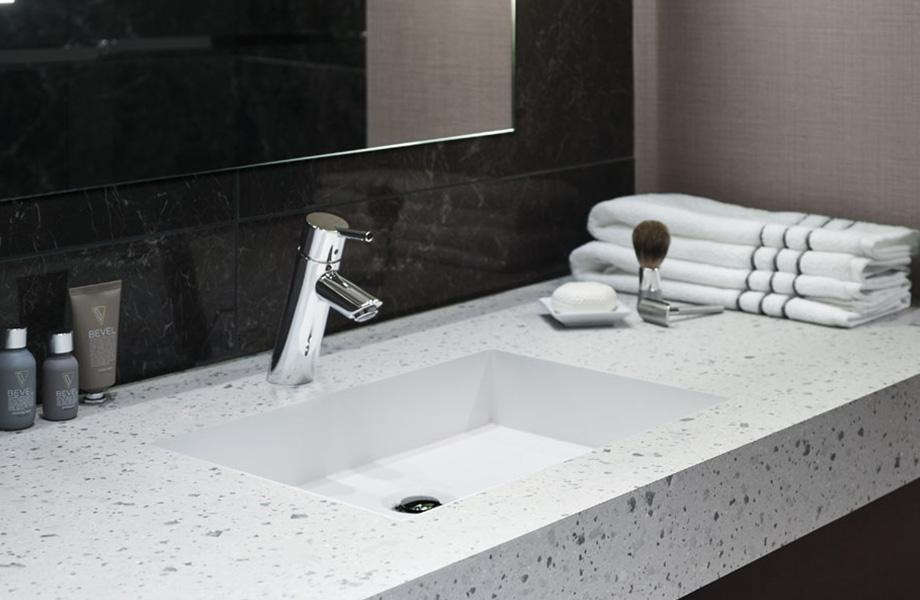 Meuble-lavabo d'une salle de bain d'hôtel avec comptoirs écoresponsables en 8812-PA Papier Terrazzo Teinté avec miroir, serviettes et articles de toilette à proximité