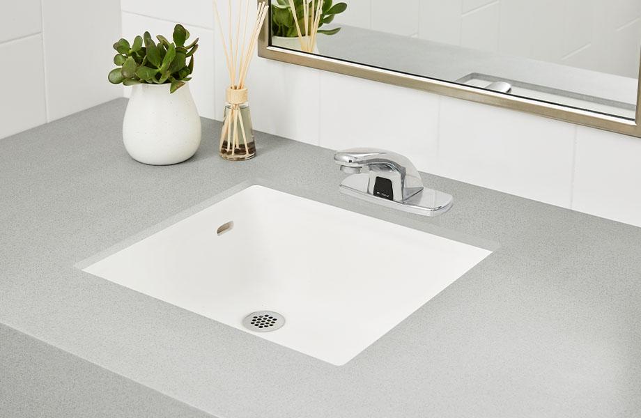 Salle de bain avec miroir, comptoir et évier intégré en surface solide 415 Luna Étain pour faciliter le maintien de la propreté dans le design des hôtels, restaurants et autres lieux de divertissement