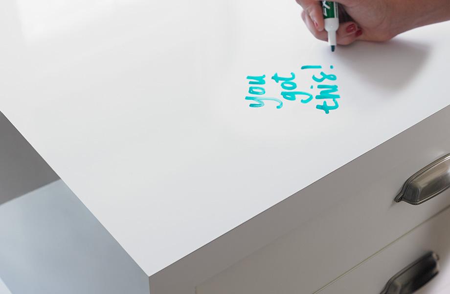 Une personne qui écrit sur un bureau en tableau blanc conçu avec le Stratifié de marque Formica 949 Blanc