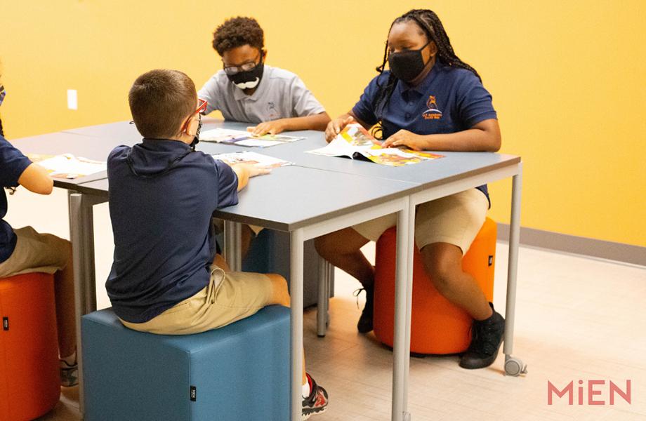 Quatre étudiants assis sur des tabourets autour d'une table de classe en Stratifié de marque Formica, conçue par MiEN