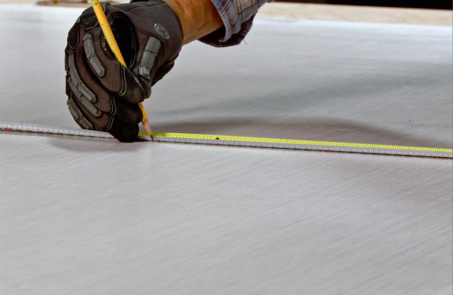 Entrepreneur mesurant avec ruban à mesurer et crayon sur un stratifié