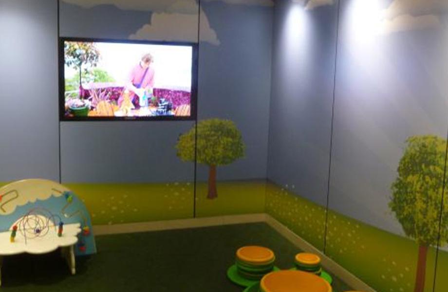 Espace de jeu pour les enfants avec jouets, télévision et panneaux muraux personnalisés Envision de Formica qui représentent un horizon gazonné avec des arbres.
