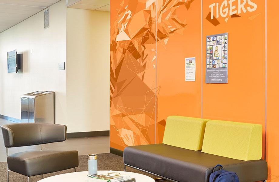 Aire d'attente avec canapé et chaise contre des panneaux Envision™ HardStop® de marque Formica de couleur orange qui mettent de l'avant un design dans le secteur de l'éducation et valorise une marque.