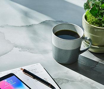 La collection des stratifiés Living Impressions™ 2020 du Groupe Formica : surface de table en stratifié 180fx® 5016-11 Aquarelle sur Porcelaine avec la tasse de café