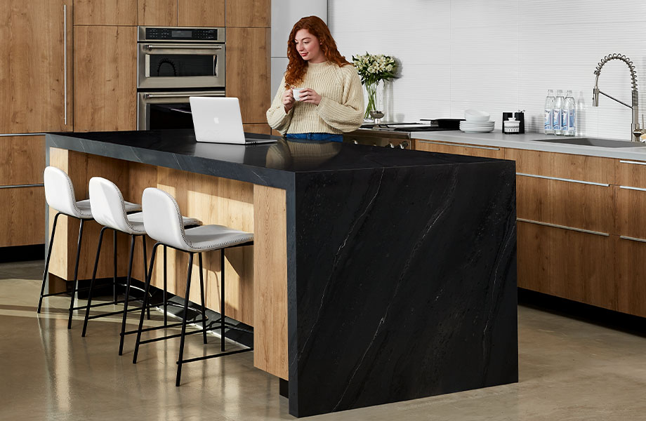5015-11 Black Painted Marble waterfall kitchen island with 9319-BH Stainless and 9312-NG Planked Urban Oak with woman