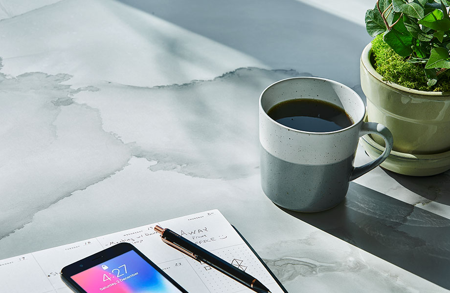 Table surface made with Formica® HPL laminate 180fx® 5016-11 Watercolor Porcelain - a soft blend of gray and beige, creating pockets of colour in the translucent overlaps. Cup of coffee, plant, phone and notebook